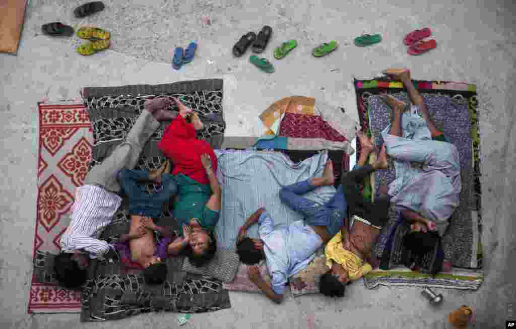 A family sleeps on the roof of a house to beat the heat in New Delhi, India. In neighborhoods with irregular electric supply and sometimes to escape the heat that gets trapped in concrete houses people often sleep outside at night.