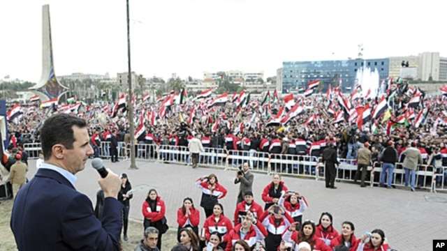 Syria's President Bashar al-Assad addresses his supporters during a surprise appearance at a rally in Umayyad Square in Damascus, January 11, 2012.