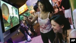 "Members of the PMS Clan, a group of professional women gamers, Alexis Hebert, seated, and Felicia Williams play an X-Box game titled ""Splinter Cell"" at the Electronic Entertainment Exposition (E3) Friday, May 12, 2006, in Los Angeles. (AP Photo/Reed Saxon)"
