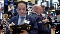Trader Tommy Kalikas, left, works on the floor of the New York Stock Exchange, Sept. 6, 2016.