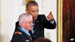 在向退役陆军中校查尔斯·凯特尔斯颁发荣誉勋章的仪式上,奥巴马与凯特尔斯开玩笑,让他面对摄像机镜头。(2016年7月18日)