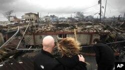 Una pareja se abraza mientras observan los escombros en Breezy Point, Nueva York, donde unas 110 casas fueron destruidas por el fuego, durante el paso de la tormenta Sandy.