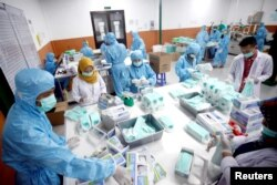 Karyawan membuat masker di sebuah pabrik, di tengah pandemi COVID-19 di Gunung Putri, Bogor, 15 April 2020. (Antara Foto/Yulius Satria Wijaya/ via REUTERS)