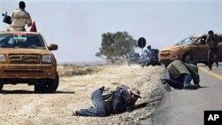 利比亚反叛力量在同亲卡扎菲军队交火中在躲避炮火攻击