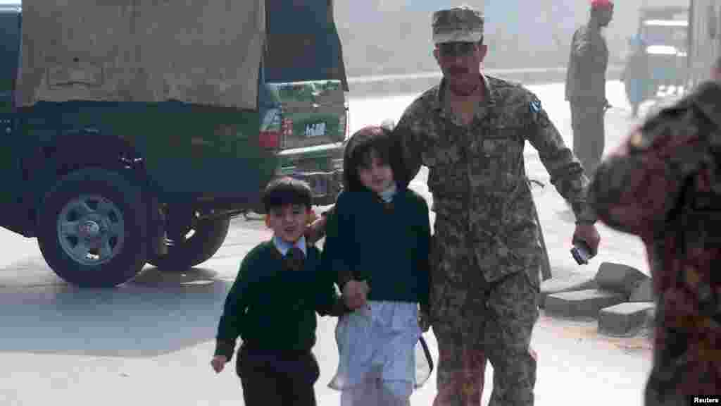 A soldier escorts schoolchildren from the school that was attacked by Taliban gunmen in Peshawar, Pakistan, Dec. 16, 2014.