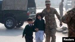 Vojnik ispraća decu iz vojne škole u Pešavaru, koju su napali pripadnici Talibana