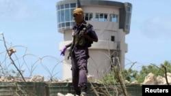 ຕຳຫຼວດຄົນໜຶ່ງຢືນຍາມຢູ່ໃກ້ກັບຫໍຄວບຄຸມການບິນ ຫຼັງຈາກເຫດລະເບີດລົດສະຫຼະຊີບ ໃກ້ກັບຖານທັບໃຫຍ່ ຂອງກອງກຳລັງຮັກສາສັນຕິພາບ ສະຫະພາບ ອາຟຣິກາ ໃນນະຄອນຫຼວງ Mogadishu, ໂຊມາເລຍ,26 ກໍລະກົດ, 2016.