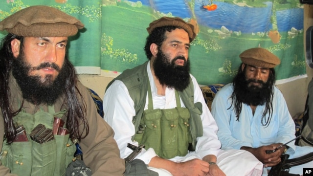 FILE - Pakistani Taliban spokesman Shahidullah Shahid, center, flanked by bodyguards, talks to reporters at undisclosed location, Pakistani tribal area of Waziristan.