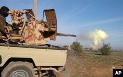 In this image posted on a militant social media account by the Al-Baraka division of the Islamic State group Feb. 24, 2015, a fighter fires a heavy weapon mounted on the back of a pickup truck during fighting in Tal Tamr, Syria.