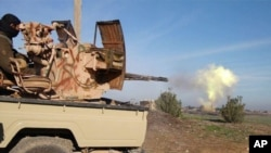 In this image posted on a militant social media account by the Al-Baraka division of the Islamic State group, Feb. 24, 2015, a fighter fires a heavy weapon mounted on the back of a pickup truck in Tal Tamr, Syria.