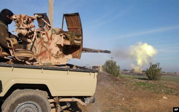 FILE - In this image posted on a militant social media account by the Al-Baraka division of the Islamic State group Feb. 24, 2015, a fighter fires a heavy weapon mounted on the back of a pickup truck during fighting in Tal Tamr, Syria.