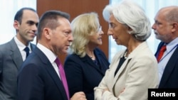 Greece's Finance Minister Yannis Stournaras talks to IMF Managing Director Christine Lagarde (R) during a eurozone finance ministers meeting in Brussels July 8, 2013.