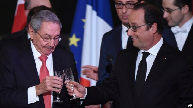 Cuban President Raul Castro, left, and French President Francois Hollande raise a glass during a state diner at the Elysee Presidential Palace in Paris, France, Feb. 1, 2016.