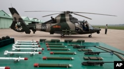 A military officer stands near a Z-9WZ attack helicopter and weapons, designed and manufactured by China, on display during a media oppotunity at a Chinese Liberation Army base, ahead of Army Day on the outskirts of Beijing.