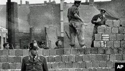图为1961年10月7日一名西柏林士兵站立在分割东、西柏林的混凝土墙边。他身后为东柏林工人正在加高围墙