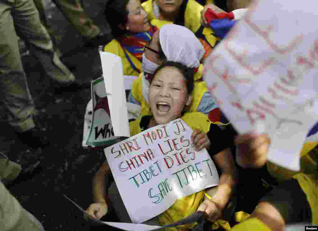 Tibetan exiles shout slogans as they struggle with police during a protest while Chinese President Xi Jinping and Indian Prime Minister Narendra Modi hold a meeting, in New Delhi, Sept. 18, 2014.