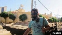 Một chiến binh phe nổi dậy mang mặt nạ chống hơi độc đi qua một chiếc xe tăng của phe chính phủ bị bắn cháy ở Idlib, ngày 13/6/2013.