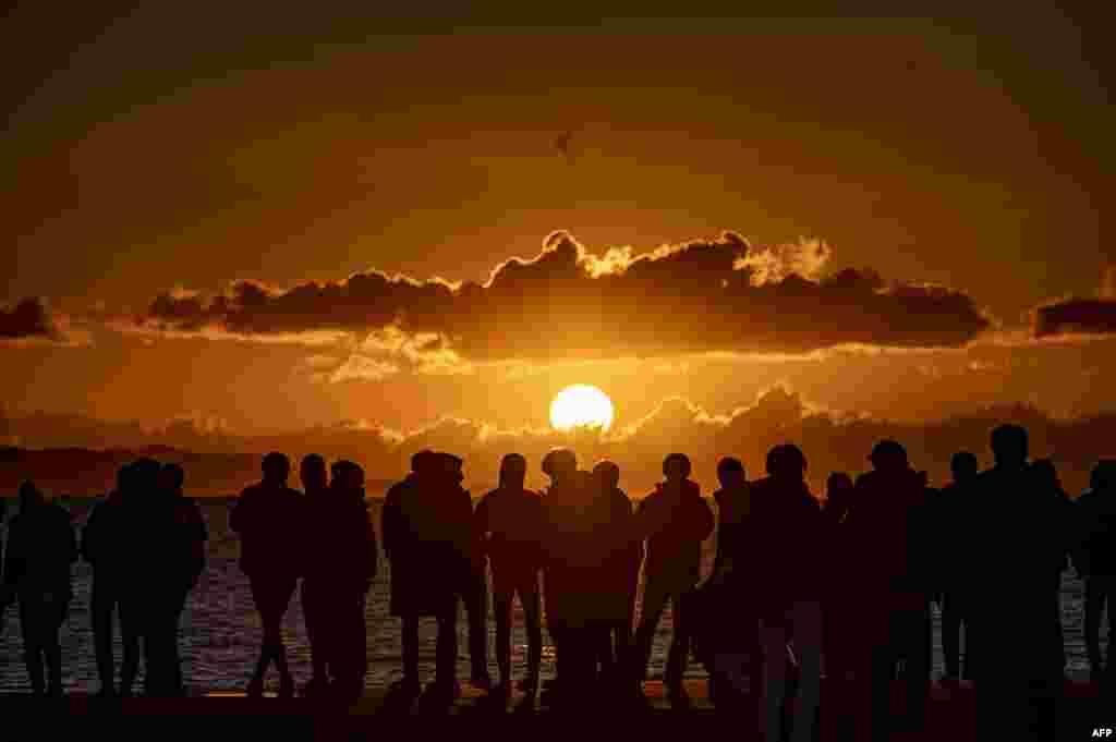 Tokionun cənub-qərbindəki Kanaqava Prefekturasında insanlar Yeni İl günündə Çiqasaki çimərliyinə toplaşıb günəşin doğmasını izləyirlər.