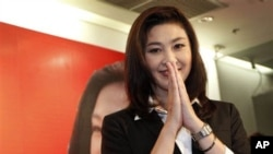 "Opposition Phue Thai party's Yingluck Shinawatra gives Thai traditional ""wai"" greeting after a press conference at the party headquarters in Bangkok, Thailand, Sunday, July 3, 2011. The apparent election result on Sunday paved the way for Yingluck Shinawa"