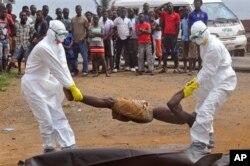 Các nhân viên y tế đặt thi thể của một người mà họ nghi là chết vì nhiễm virus Ebola vào một chiếc túi đựng.