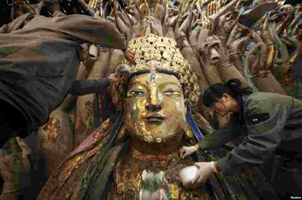Restoration workers peel off loose gold foil as part of a restoration project for an 800-year-old Thousand-Hand Guanyin Buddhist statue on Mount Baoding in Chongqing municipality, China. The stone statue, which takes up about 88 square meters on the mountain, dates back to the Southern Song Dynasty (1127-1279).