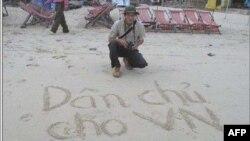 """Blogger Ðiếu Cày và dòng chữ """"Dân chủ cho Việt Nam"""" viết trên cát"""
