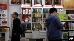 FILE - Customers walk past portraits of Mao Zedong displayed at a bookstore in Beijing. Authorities in China have ordered books by Chinese-American scholar Yu Ying-shih and several others to be removed from sale.