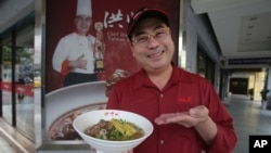 Chef Hung shows pineapple beef noodle outside of his restaurant in Taipei, Taiwan, Wednesday, March 10, 2021. (AP Photo/Chiang Ying-ying)