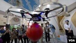 在北京舉行的中國國際模型博展會上,參觀者觀看由手機操縱的無人機。