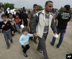 Syrian families carry their belongings as they arrive by foot in Wadi Khaled area, northern Lebanon, near the Lebanese-Syrian border, April 28, 2011.