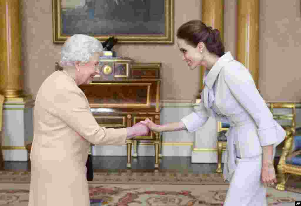 U.S actress Angelina Jolie, right, is presented with the Insignia of an Honorary Dame Grand Cross of the Most Distinguished Order of St. Michael and St. George by Britain's Queen Elizabeth II at Buckingham Palace, London.