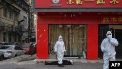 身穿防护服的中国卫生官员在检查一名在武汉一所医院附近倒地死亡的老年男子。(2020年1月30日)