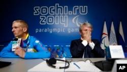 Atlet paralimpik Ukraina Grygorii Vovchinskyi menunjukkan tanda pengenalnya saat Presiden Komite Nasional Paralimpik Ukraina Valeriy Sushkevich menutup wajahnya dengan kedua belah tangannya dalam konferensi pers di Sochi (7/3).