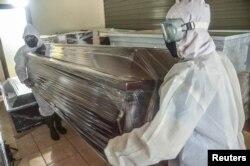 Para pekerja mengatur peti jenazah untuk korban virus corona (COVID-19) di Bekasi, Jawa Barat, 1 April 2020. (Foto: Antara via Reuters)