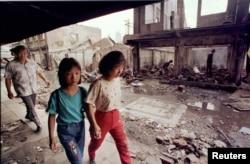 Warga etnis Tionghoa melewati rumah-rumah yang hancur dijarah dan dibakar massa dalam kerusuhan, 26 Mei 1998. (Foto: Reuters/Arsip)