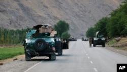 在阿富汗北部巴達赫尚市附近與塔利班交戰的前線,阿富汗政府士兵在路上暫停。(2021年7月4日)