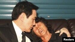 Taiwan's President Ma Ying-jeou (L) consoles Hung Chen A-lun, widow of the Taiwanese fisherman Hung Shih-cheng who was shot dead by Filipino coast guards last week, when visiting the victim's family at Liuqiu in Pingtung County, southern Taiwan, May 12, 2