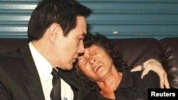 Presiden Taiwan Ma Ying-jeou (kiri) menghibur Hung Chen A-lun, janda nelayan Taiwan Hung Shih-cheng yang ditembak penjaga pantai Filipina saat mengunjungi keluarga korban di Liuqiu, wilayah Pingtung, Taiwan selatan (12/5).