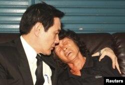 台湾总统马英九(左)2013年5月12日前往屏东县小琉球的一个于上个星期被菲律宾海岸警卫队枪杀的台湾渔民洪石成的家中安慰受害者的遗孀