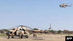 FILE - Mi-8 attack helicopters are seen in Fotokol, Cameroon, after an operation in nearby Gambaru, Nigeria. Chadian aircraft struck Boko Haram positions in the Nigerian border town for a second straight day, Feb. 1, 2015.