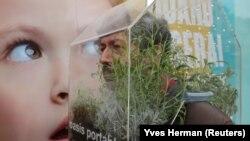 """Seniman Belgia, Alain Verschueren, mengenakan """"Oasis Portabel"""" karena ingin berada di gelembungnya saat berada di tengah kota di tengah wabah virus corona, di Brussels, Belgia, 16 April 2021. (Foto: Yves Herman/Reuters)"""