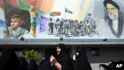 Iranian female worshippers join a rally after their Friday prayers to condemn Saudi-led airstrikes against Yemen, under a mural of the late Iranian revolutionary founder Ayatollah Khomeini and Basij paramilitary force, in Tehran, April 3, 2015.