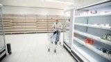 Un cliente empuja su carrito junto a los estantes vacíos en una tienda de Sainsbury's durante el brote de COVID-19, en Harpenden, Reino Unido, el 18 de marzo de 2020.