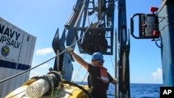 Anh Tucker Bailey điều chỉnh một dây cáp qua ròng rọc trong khi triển khai tìm kiếm các mảnh vỡ của con tàu chở hàng mất tích El Faro.