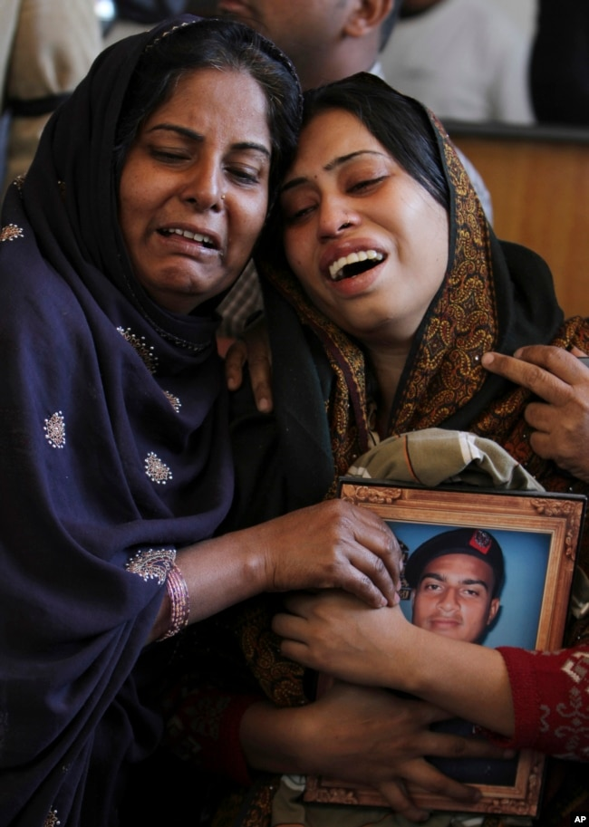 FILE - Pakistani women mourn the death of a family member during a funeral in Karachi, Pakistan, Jan. 18, 2013. The shooting death of Shahzeb Khan, 20, in one of Karachi's most upscale neighborhoods highlighted a growing trend of citizens using social media to hold the country's rich and powerful to account.