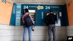 2013年3月27日人们在塞浦路斯首都尼科西亚塞浦路斯银行一家关门的分行外边使用ATM提款机提款