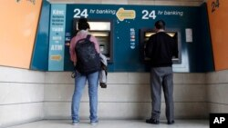 People use ATMs outside a closed branch of the Bank of Cyprus in capital Nicosia, Cyprus, Mar. 27, 2013.