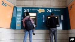 Para nasabah Bank Siprus menggunakan ATM di ibukota Nicosia (27/3). Siprus membatasi jumlah transfer uang nasabah dari Siprus ke negara lain.