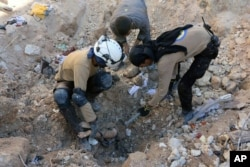 In this photo provided by the Syrian Civil Defense group known as the White Helmets, shows members of Civil Defense removing a dead body from under the rubble after airstrikes hit in Aleppo, Sept. 24, 2016.