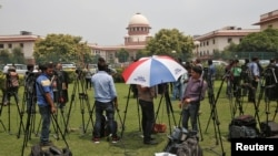 Television journalists are seen outside the Supreme Court building in New Delhi, India, Aug. 22, 2017.